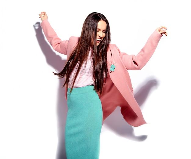 Portrait de la belle femme brune souriante caucasienne modèle en pardessus rose vif et jupe bleue élégante d'été