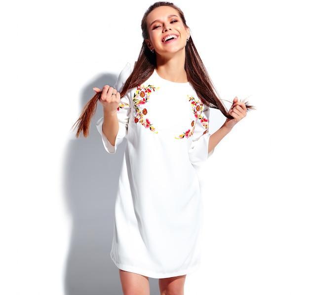 Portrait de la belle femme brune souriante caucasienne modèle en robe élégante d'été blanc. tordant ses cheveux