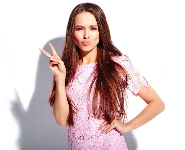 Portrait de la belle femme brune souriante caucasienne modèle en robe élégante d'été rose vif isolé sur fond blanc. montrer le signe de la paix et faire face au canard