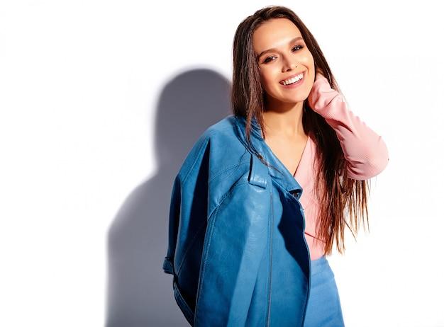 Portrait de la belle femme brune souriante caucasienne modèle en vêtements élégants d'été rose et bleu vif isolé sur fond blanc