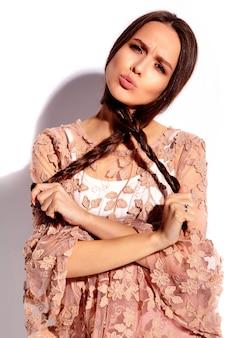 Portrait de la belle femme brune souriante caucasienne modèle en vêtements élégants d'été rose vif isolé sur fond blanc.