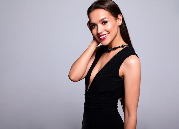 Portrait de la belle femme brune souriante modèle en robe noire avec maquillage de soirée et et lèvres rouges isolé sur gris
