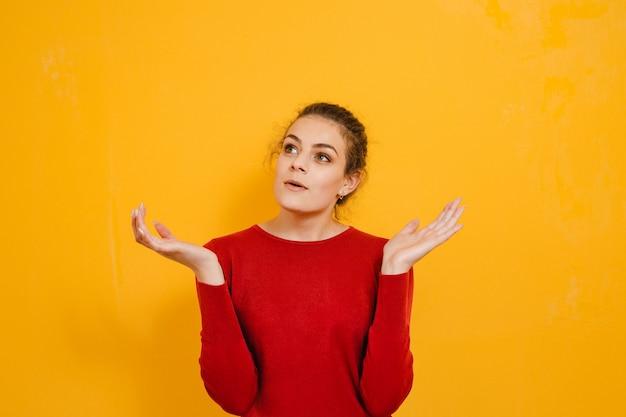 Portrait d'une belle femme brune souriante et montrant des gestes sur le mur jaune