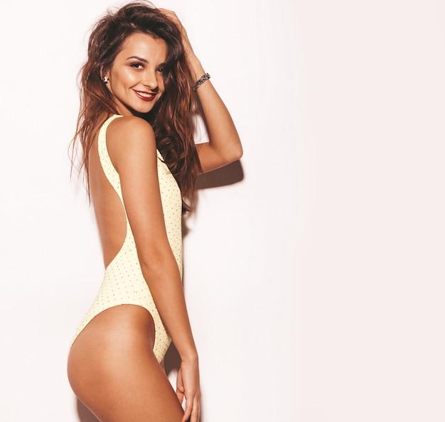 Portrait de belle femme brune souriante sexy. fille vêtue de lingerie décontractée de corps jaune d'été. modèle isolé