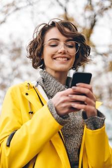 Portrait de la belle femme brune taper un sms ou faire défiler le flux dans le réseau social à l'aide de son smartphone tout en étant en plein air