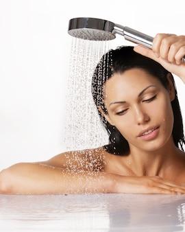 Portrait d'une belle femme brune tient la douche dans les mains avec de l'eau qui tombe