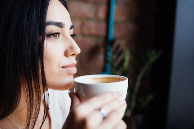 Portrait de la belle femme buvant du café au café moderne