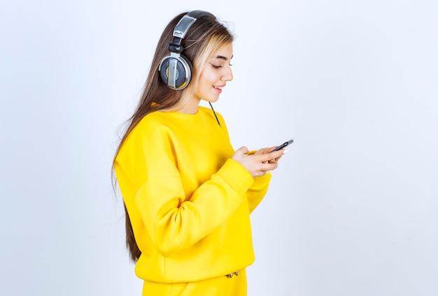 Portrait d'une belle femme avec un casque à l'aide d'un téléphone portable