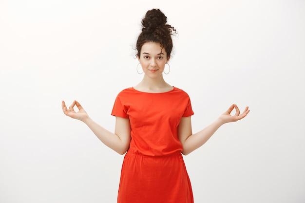 Portrait de belle femme caucasienne calme avec des cheveux bouclés, écartant les mains en geste zen et souriant avec une expression intriguée, relaxant