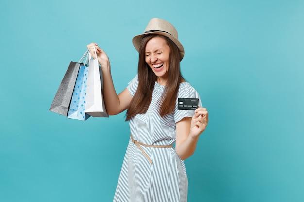 Portrait d'une belle femme caucasienne en robe d'été, chapeau de paille tenant des sacs de paquets avec des achats après le shopping, carte de crédit bancaire isolée sur fond bleu pastel. copiez l'espace pour la publicité.