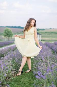 Portrait d'une belle femme caucasienne romantique de 25 ans avec de longs beaux cheveux, vêtue d'une robe beige, marchant dans un champ féerique de lavande