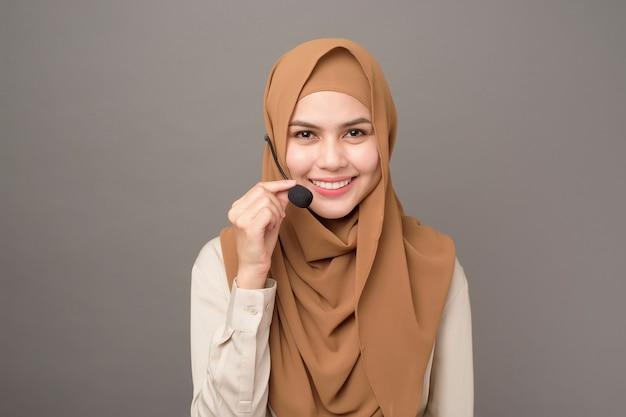 Portrait de la belle femme de centre d'appel avec hijab sur gris