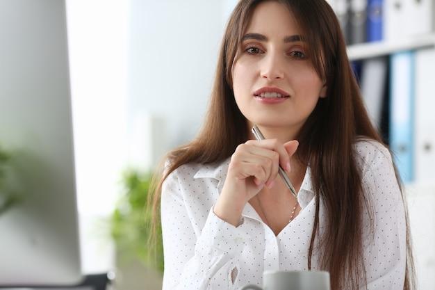 Portrait de la belle femme en chemisier classique blanc au bureau