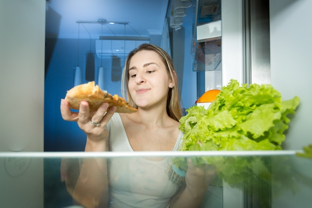Portrait de belle femme choisissant entre pizza et salade fraîche. vue de l'intérieur du réfrigérateur. concept d'aliments sains et malsains.