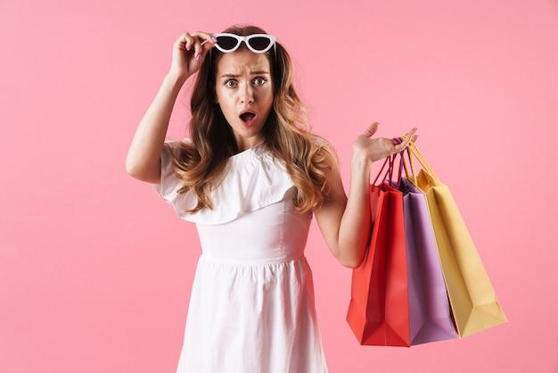 Portrait d'une belle femme choquée vêtue d'une robe blanche tenant des sacs à provisions et des lunettes de soleil isolées sur un mur rose