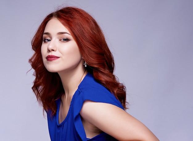 Portrait de la belle femme avec une coiffure frisée et un maquillage lumineux,