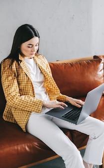 Portrait de belle femme concentrée assise sur un canapé