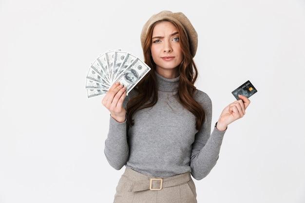 Portrait d'une belle femme confuse tenant de l'argent et une carte de crédit isolée sur un mur blanc.