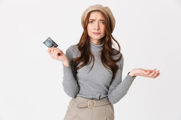 Portrait d'une belle femme confuse tenant une carte de crédit isolée sur un mur blanc.