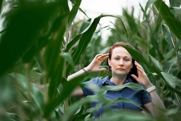 Portrait de la belle femme dans un champ de maïs vert