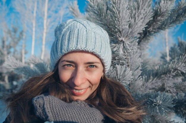Portrait d'une belle femme dans un chapeau sur la forêt d'hiver