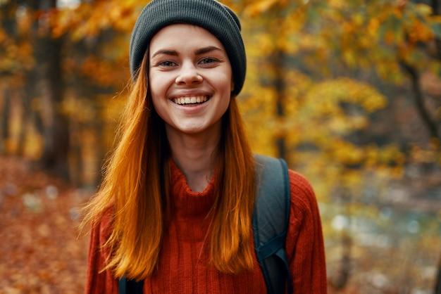 Portrait d'une belle femme dans un pull chapeau avec un sac à dos sur le dos dans la forêt d'automne en
