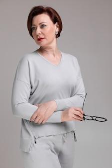 Portrait de belle femme dans des vêtements légers avec des lunettes dans la main isolée