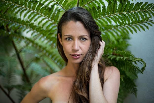 Portrait de belle femme debout à l'extérieur contre les plantes vertes