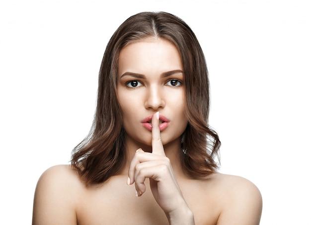 Portrait de la belle femme avec le doigt sur les lèvres, isolé