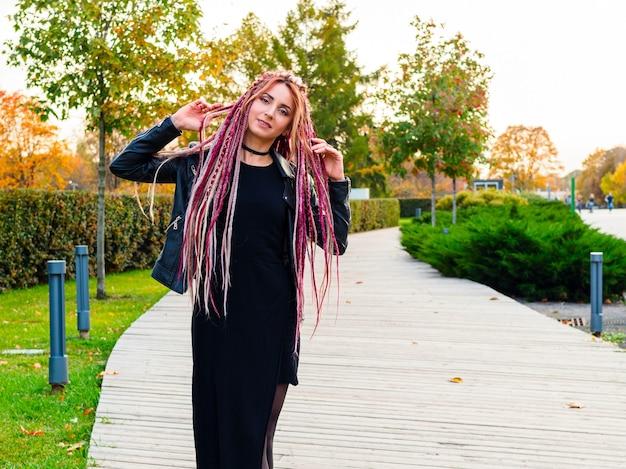 Portrait de belle femme avec des dreadlocks roses et des nattes dans un parc au début de l'automne modèle mignon
