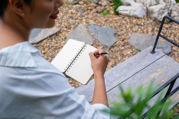 Portrait d'une belle femme écrivant dans un livre sont assis en pensant au travail dans le parc, se détendre en plein air concept de temps.
