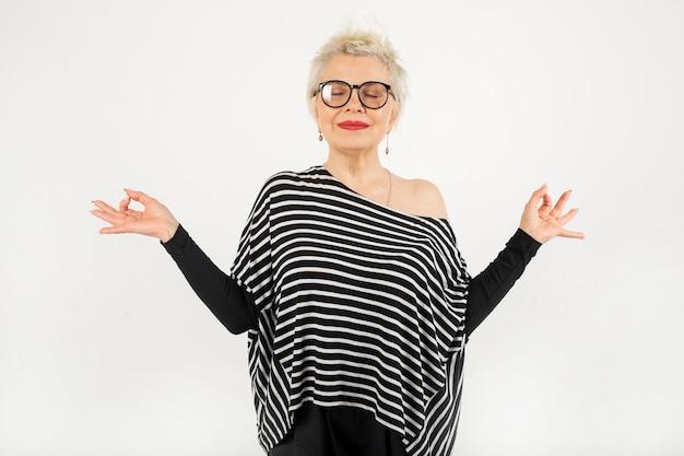 Portrait d'une belle femme élégante âgée dans des verres avec un geste de la main