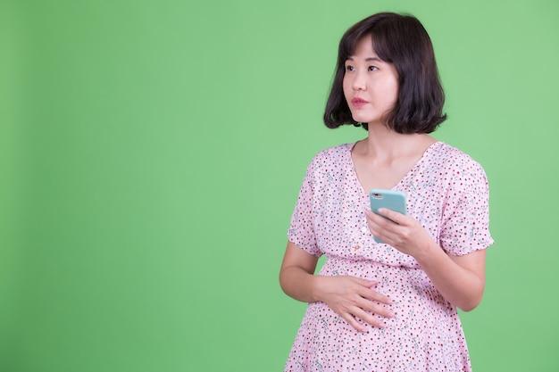 Portrait de la belle femme enceinte asiatique aux cheveux courts contre la chrominance ou le mur vert