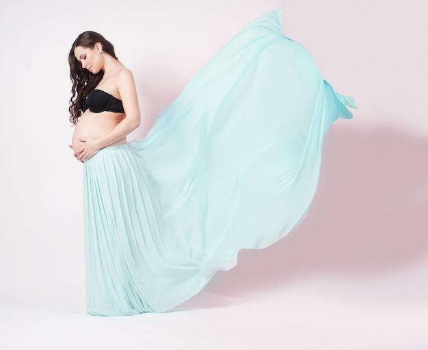 Portrait d'une belle femme enceinte en châle en mousseline bleue