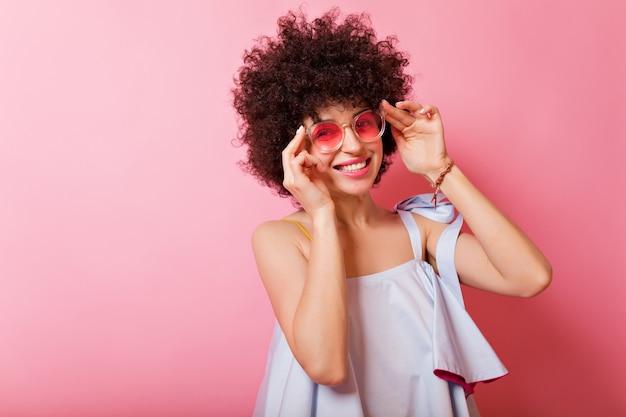 Portrait de belle femme ensoleillée aux cheveux courts bouclés et charmant sourire porte chemise bleue et lunettes roses pose sur rose