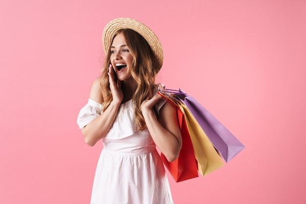 Portrait d'une belle femme étonnée portant un chapeau de paille se demandant et tenant des sacs à provisions isolés sur un mur rose