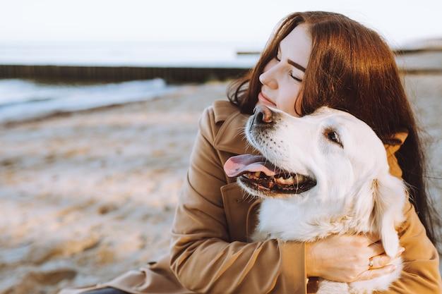 Portrait de belle femme étreignant avec son chien golden retreiver