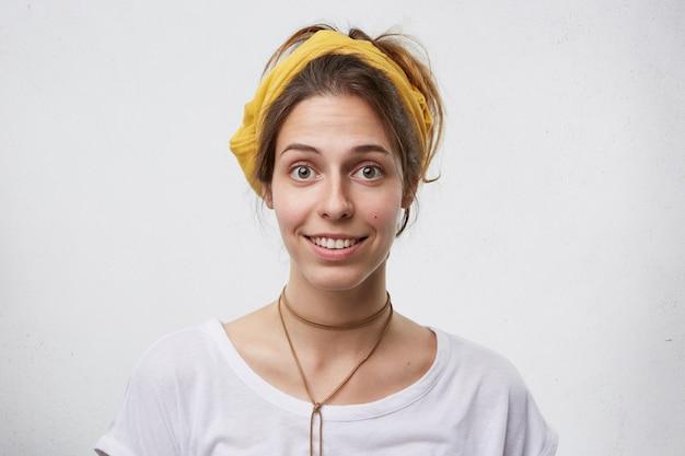 Portrait de la belle femme européenne ayant les cheveux noirs attachés à la recherche avec ses grands yeux bruns et doux sourire isolé