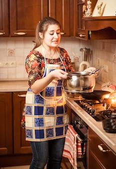 Portrait de belle femme exerçant son soupe dans une casserole en métal
