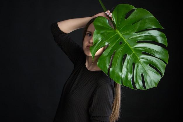 Portrait de la belle femme avec des feuilles tropicales vertes sur fond noir