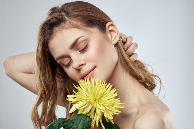 Portrait d'une belle femme avec une fleur jaune sur un modèle de sourire charmant léger cheveux rouges