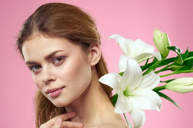 Portrait d'une belle femme avec des fleurs blanches dans ses mains sur une vue recadrée rose