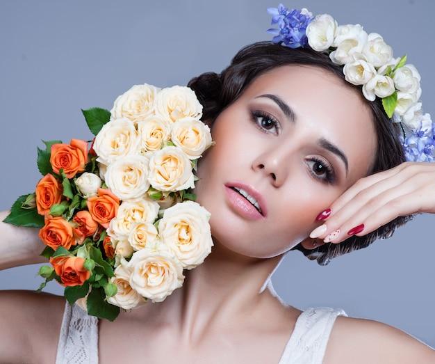 Portrait d'une belle femme avec des fleurs dans les cheveux.
