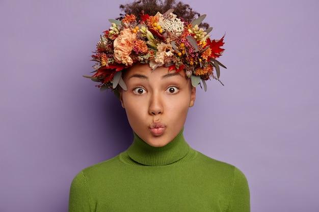 Portrait de belle femme frisée garde les lèvres arrondies, a la peau foncée saine, porte la couronne d'automne, fait la grimace, habillée en col roulé vert.