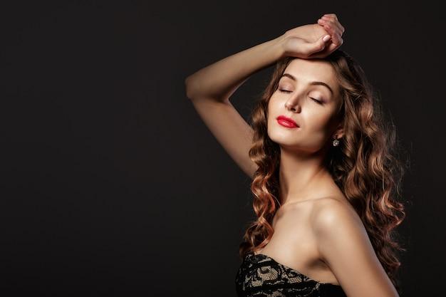 Portrait de la belle femme frisée heureuse en robe noire ferma les yeux avec plaisir