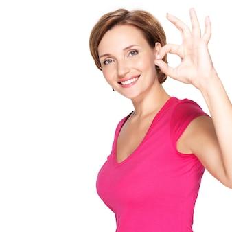 Portrait d'une belle femme heureuse adulte avec un geste ok sur un mur blanc