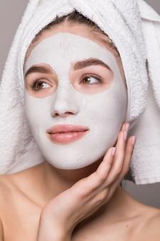 Portrait de la belle femme heureuse après la douche avec une serviette sur la tête avec un masque à la crème sur le visage