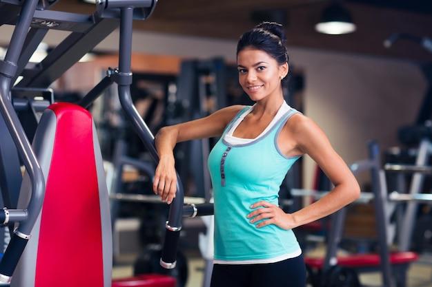 Portrait d'une belle femme heureuse debout dans une salle de fitness