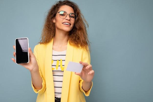 Portrait d'une belle femme heureuse portant une veste jaune et des lunettes optiques isolées sur un mur de fond tenant et montrant un téléphone avec un écran vide et une carte de crédit regardant la caméra