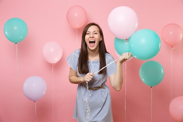 Portrait d'une belle femme heureuse ravie en robe rayée bleue criant tenant des ballons à air colorés sur fond rose tendance lumineux. fête d'anniversaire, concept d'émotions sincères.